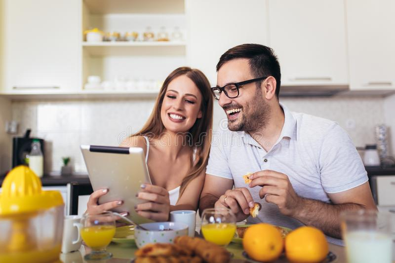 Couple enjoying breakfast time together at home and using digital tablet stock photo