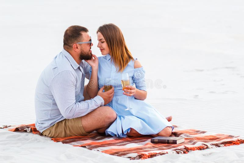 Happy couple enjoying picnic on the white sand beach and drinking wine or champagne during romantic dinner, young couple kissing royalty free stock photos