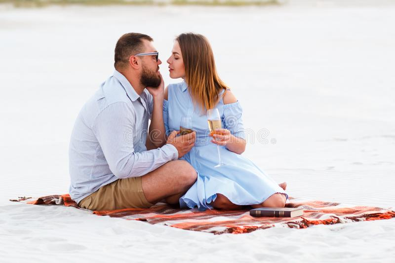 Happy couple enjoying picnic on the white sand beach and drinking wine or champagne during romantic dinner, young couple kissing royalty free stock images