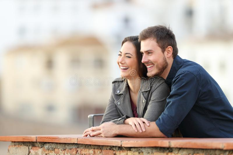 Happy couple enjoying views in a terrace on vacation. Happy couple enjoying views in a rural apartment terrace on vacation stock image