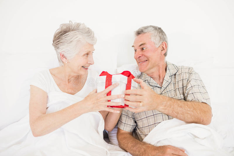 Happy couple exchanging gift. At bed stock photo
