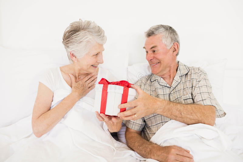 Happy couple exchanging gift. At bed stock image
