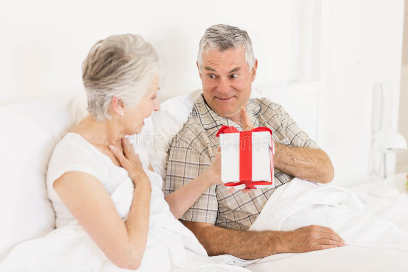 Happy couple exchanging gift. At bed stock photos