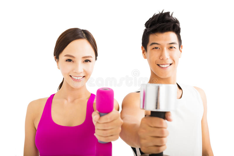 Happy couple exercising with dumbbell. Young happy couple exercising with dumbbell stock photo