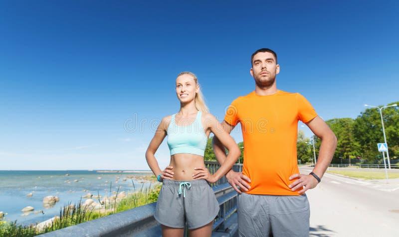 Happy couple exercising at summer seaside royalty free stock photo