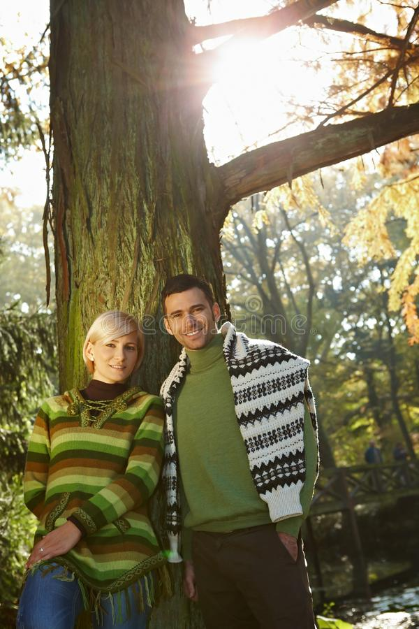 Happy couple in fall forest outdoor low angle. Happy casual caucasian couple in fall forest outdoor low angle. Smiling, standing, looking at camera, sun flare royalty free stock photography