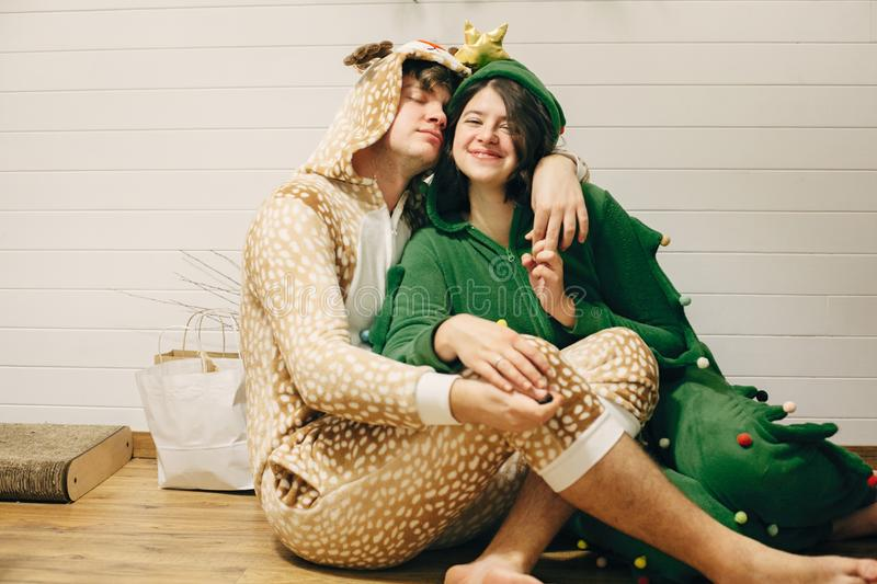 Happy couple in festive pajamas having fun at christmas gifts, sitting on floor. Celebrating Christmas or New Year eve. Man in stock images