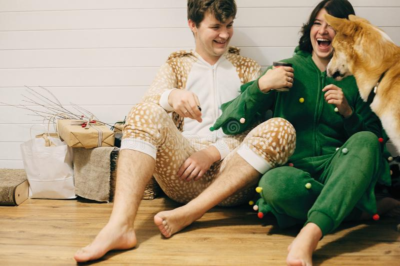 Happy couple in festive pajamas having fun and feeding pets with canned food. Celebrating Christmas or New Year eve together with stock image