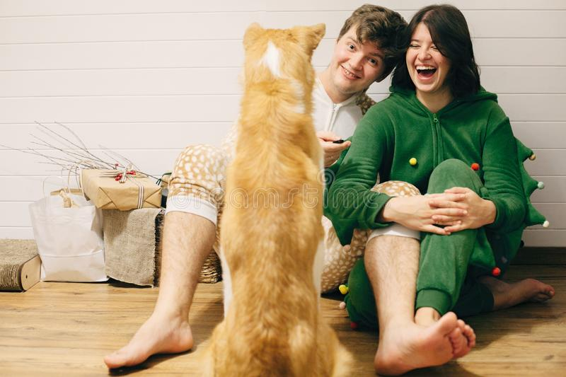 Happy couple in festive pajamas having fun and feeding their dog with canned food in room. Celebrating Christmas or New Year eve royalty free stock photo