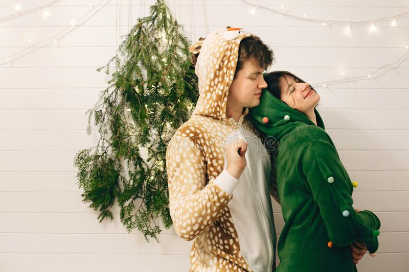 Happy couple in festive pajamas hugging at christmas tree lights in stylish room. Celebrating Christmas or New Year eve, funny royalty free stock image