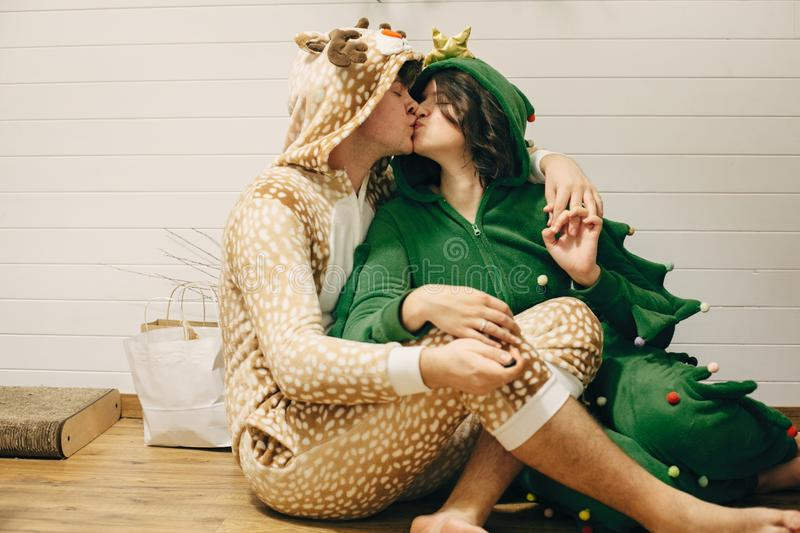 Happy couple in festive pajamas kissing at christmas gifts, sitting on floor. Celebrating Christmas or New Year eve. Man in deer stock photography