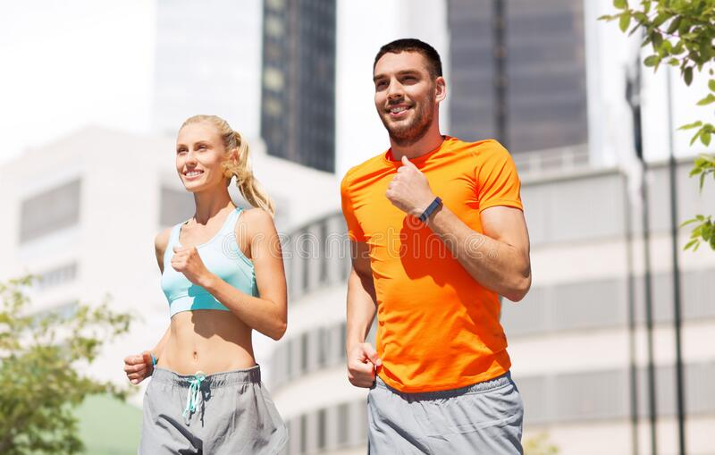 Happy couple with fitness trackers running at city stock photography