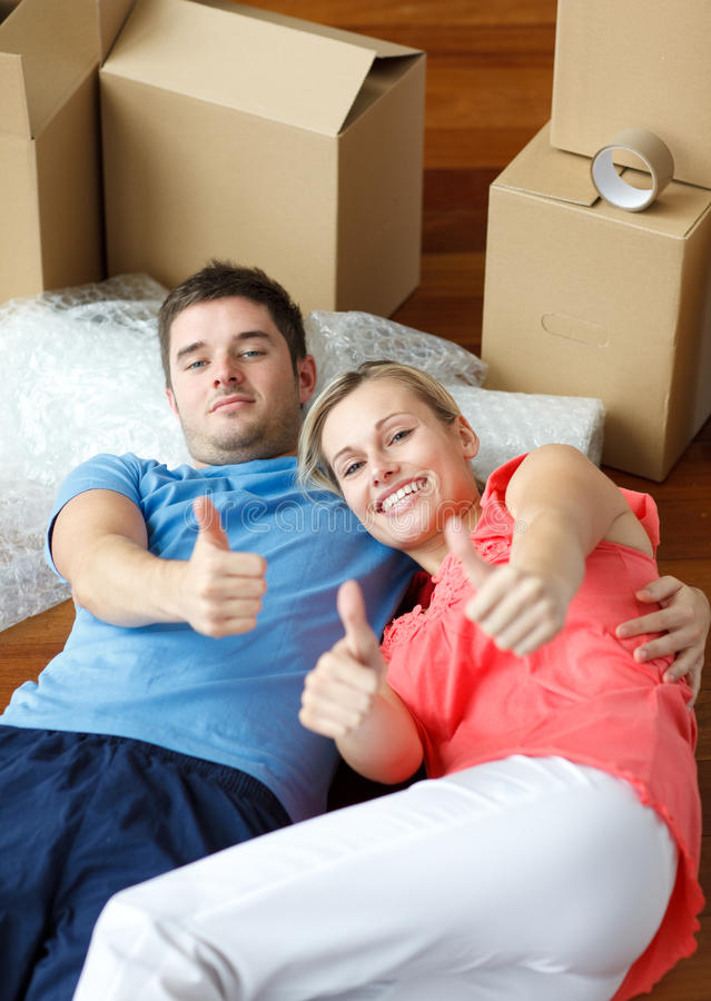 Happy couple on floor after moving with thumbs up stock image