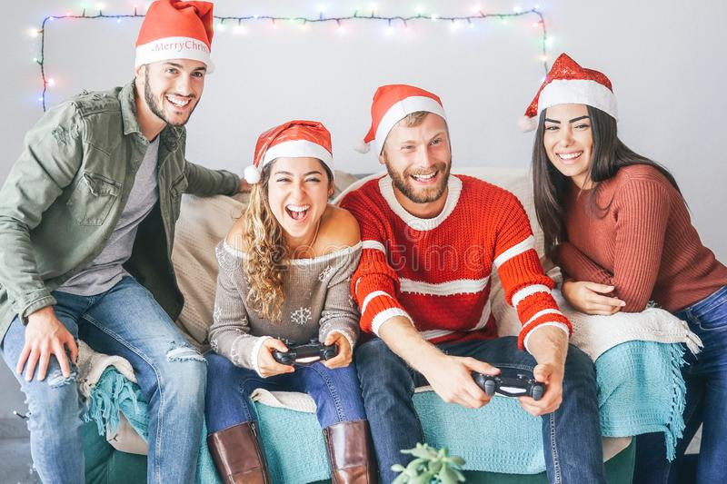 Happy couple of friends playing video games during christmas time at home - Young people having fun with new trends technologies royalty free stock images