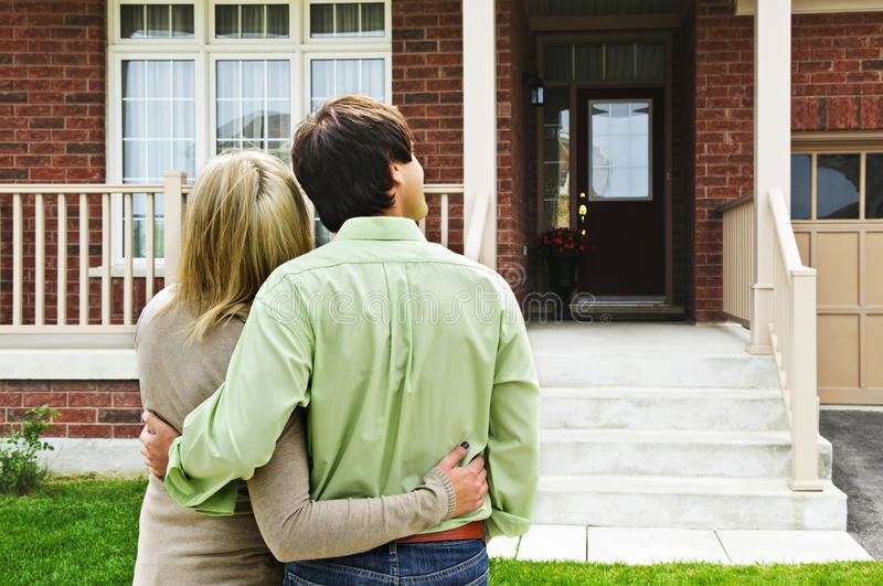 Happy couple in front of home stock image