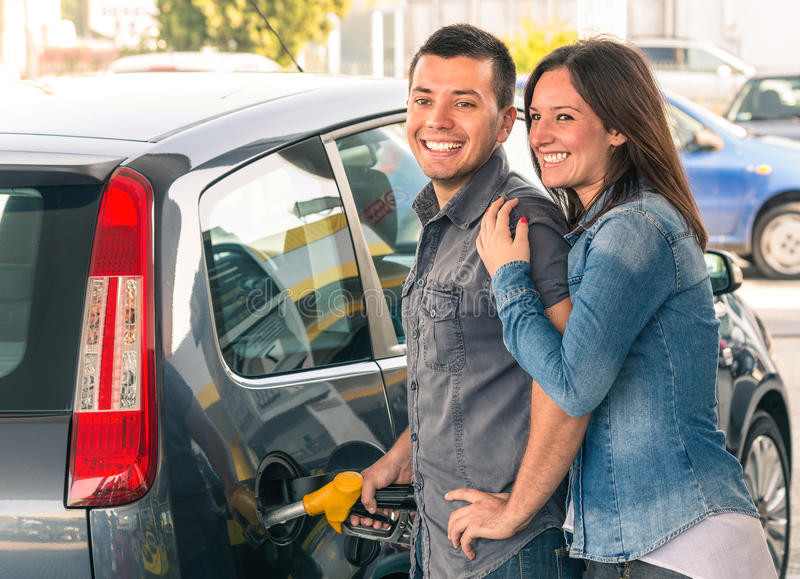 Happy couple at fuel station pumping gasoline at gas pump. Portrait of young men and women of men filling modern car at gasoline tank royalty free stock image