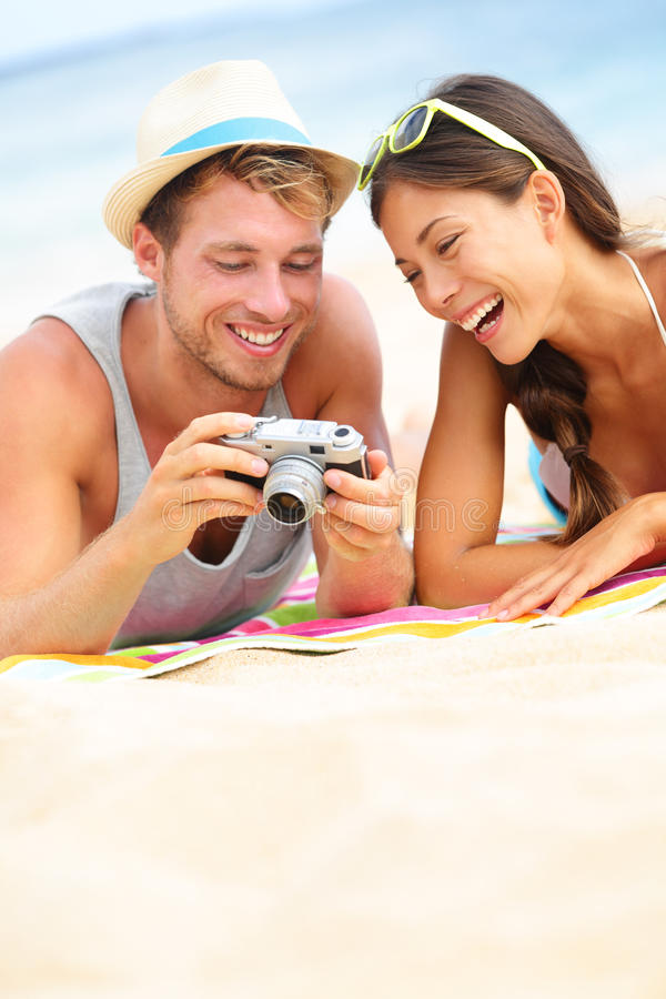 Happy couple fun on beach looking at camera. Happy couple fun on beach laughing together looking at summer vacation travel photo pictures on retro vintage camera royalty free stock photo