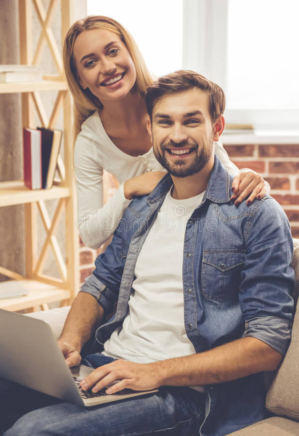 Happy couple with gadget. Beautiful couple is using a laptop, looking at camera and smiling while spending time together at home stock image