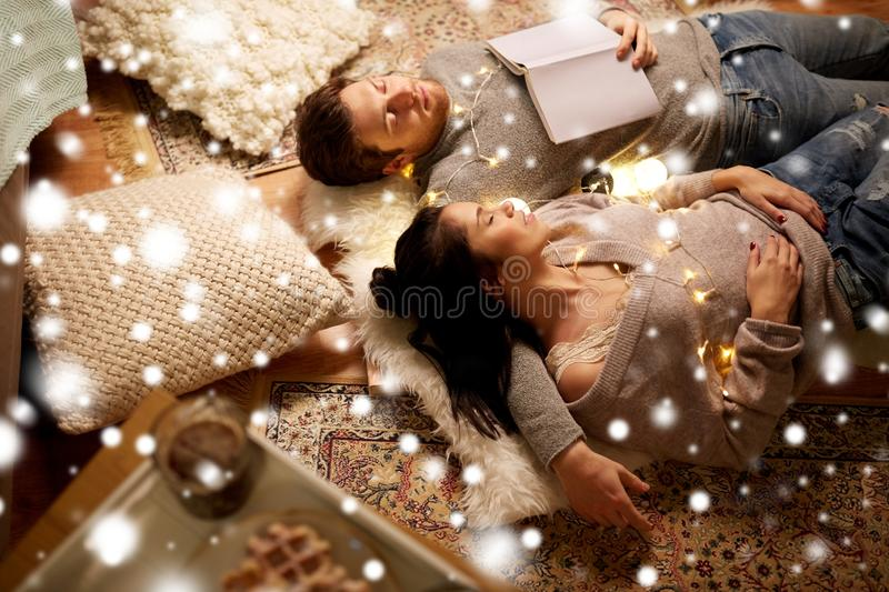 Happy couple with garland lying on floor at home royalty free stock photos