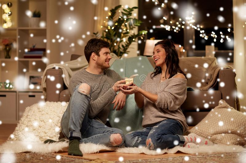 Happy couple with gift box at home stock image