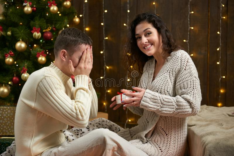 Happy couple give gifts in christmas decoration, sitting on floor in dark wooden interior with lights. Romantic evening and love c royalty free stock photos