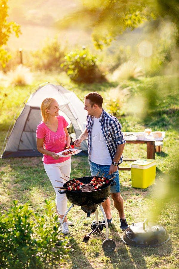 Happy couple grilling meat. On a barbecue stock image