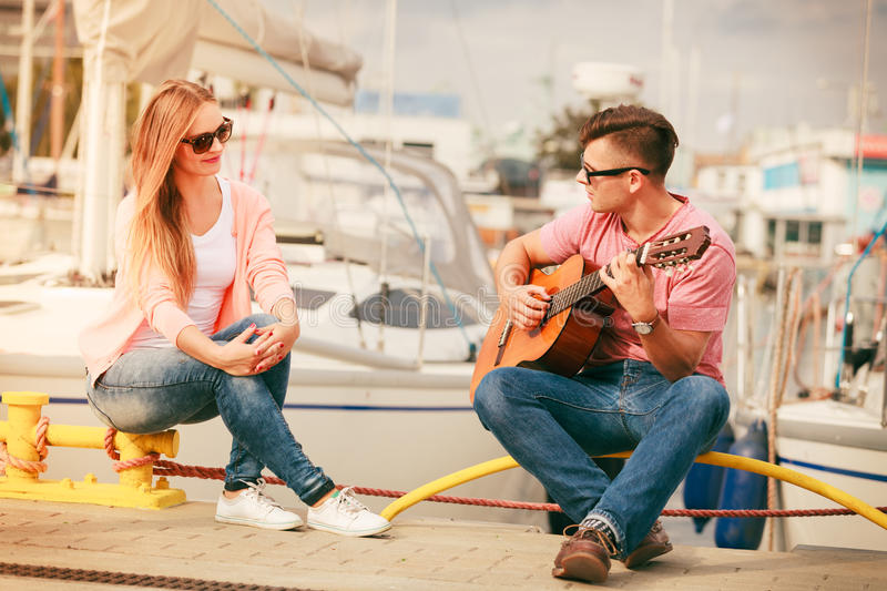 Happy couple with guitar outdoor. Instruments and musical concept. Young happy couple with classic guitar dating outdoor at sea stock photo
