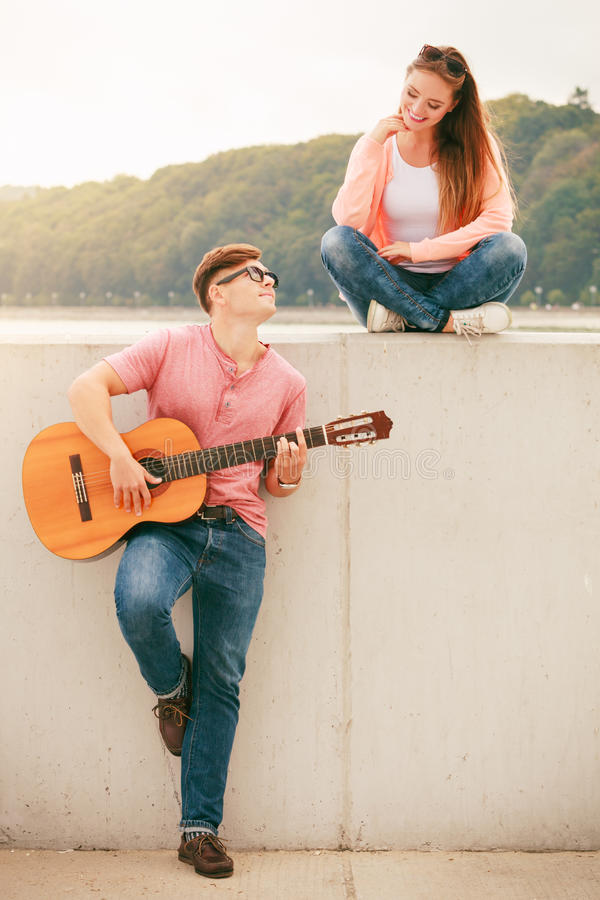 Happy couple with guitar outdoor. Instruments and musical concept. Young happy couple with instrument men playing classic guitar dating outdoor at stock image