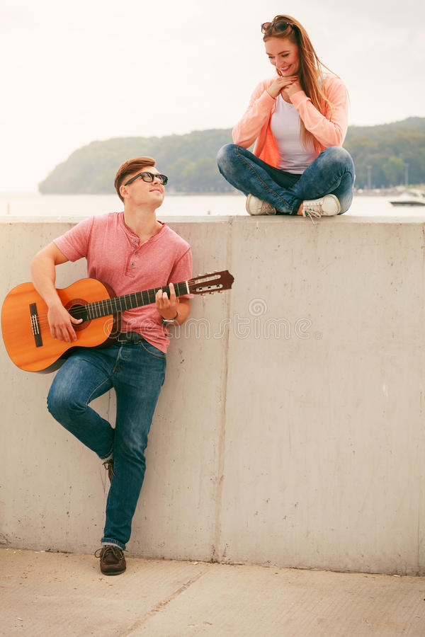 Happy couple with guitar outdoor. Instruments and musical concept. Young happy couple with instrument men playing classic guitar dating outdoor at stock photo