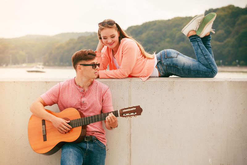 Happy couple with guitar outdoor. Instruments and musical concept. Young happy couple with instrument men playing classic guitar dating outdoor at sea royalty free stock images