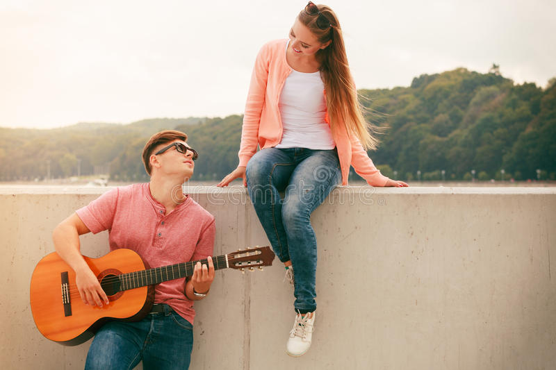 Happy couple with guitar outdoor. Instruments and musical concept. Young happy couple with instrument men playing classic guitar dating outdoor at sea stock image