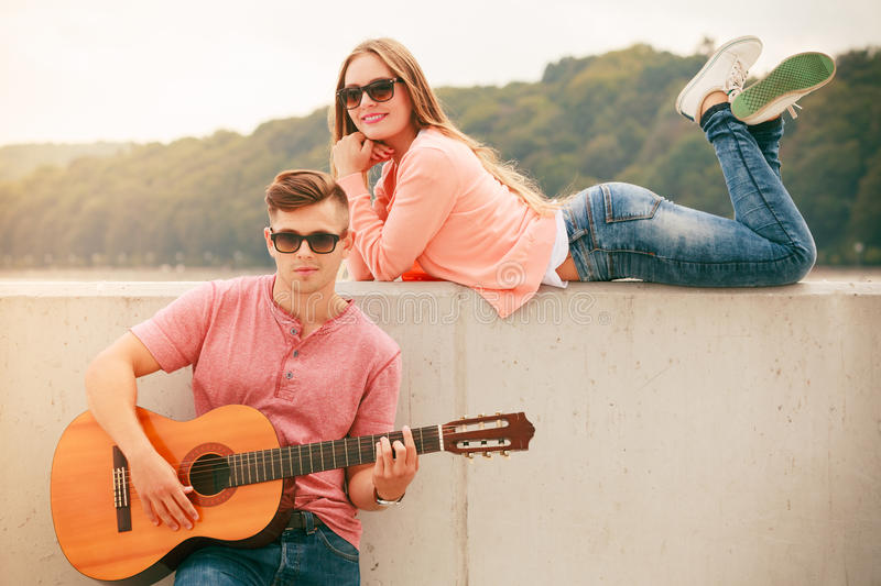 Happy couple with guitar outdoor. Instruments and musical concept. Young happy couple with instrument men playing classic guitar dating outdoor at sea royalty free stock image