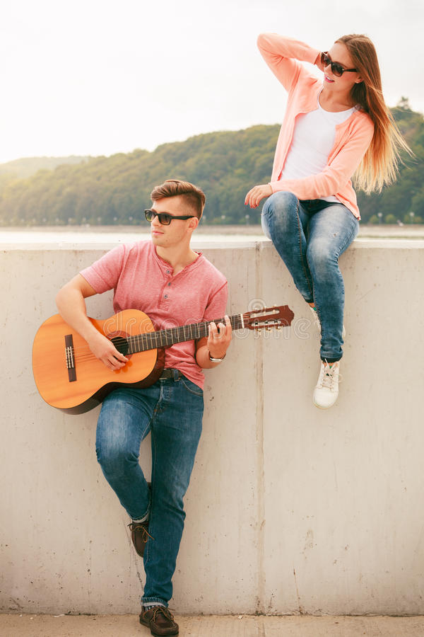 Happy couple with guitar outdoor. Instruments and musical concept. Young happy couple with instrument men playing classic guitar dating outdoor at sea stock photography