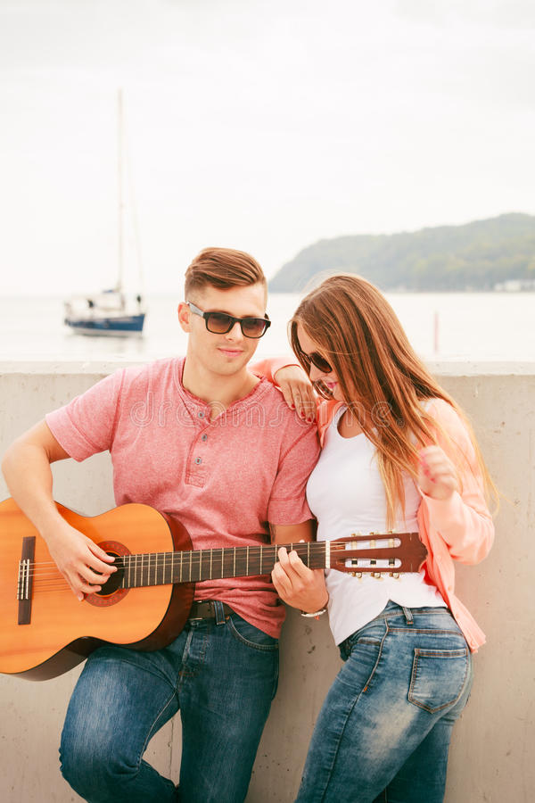 Happy couple with guitar outdoor. Instruments and musical concept. Young happy couple with instrument men playing classic guitar dating outdoor at sea stock images