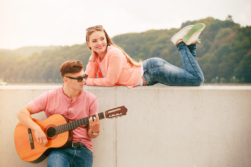 Happy couple with guitar outdoor. Instruments and musical concept. Young happy couple with instrument men playing classic guitar dating outdoor at sea royalty free stock photography