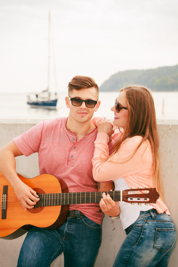 Happy couple with guitar outdoor. Instruments and musical concept. Young happy couple with instrument men playing classic guitar dating outdoor at sea stock photos