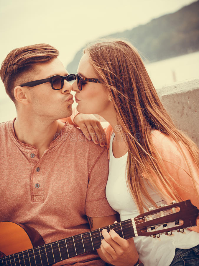 Happy couple with guitar outdoor. Instruments and musical concept. Young happy kissing couple with instrument men playing classic guitar dating outdoor at sea stock photo