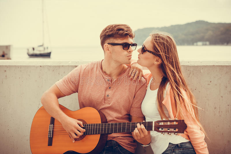 Happy couple with guitar outdoor. Instruments and musical concept. Young happy kissing couple with instrument men playing classic guitar dating outdoor at sea stock photography