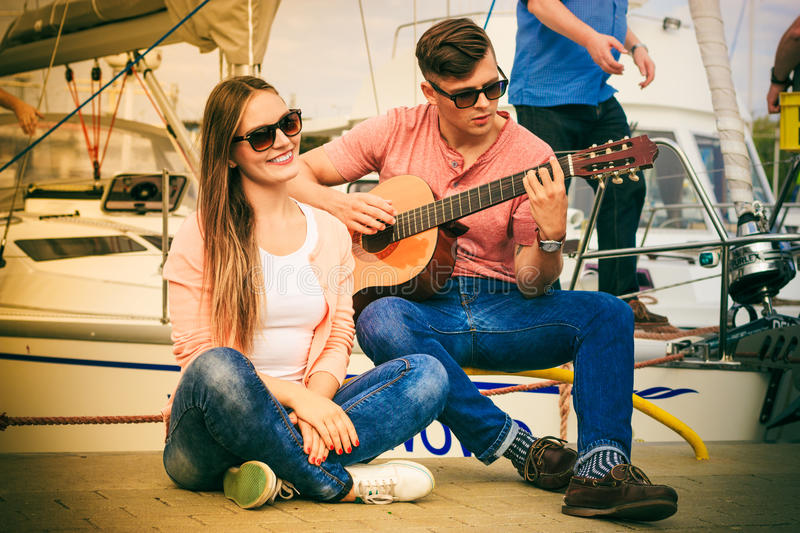Happy couple with guitar outdoor. Musical date concept. Young happy couple with instrument men playing classic guitar dating outdoor at sea stock photo