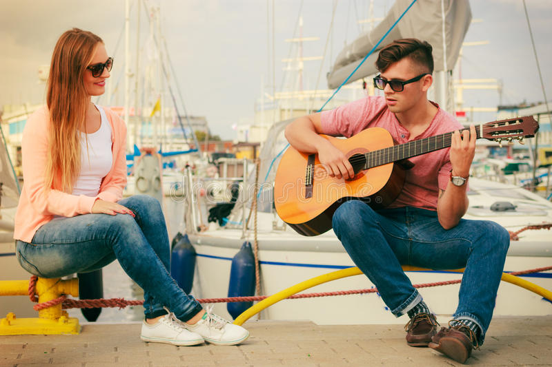 Happy couple with guitar outdoor. Musical date concept. Young happy couple with instrument men playing classic guitar dating outdoor at sea royalty free stock photography