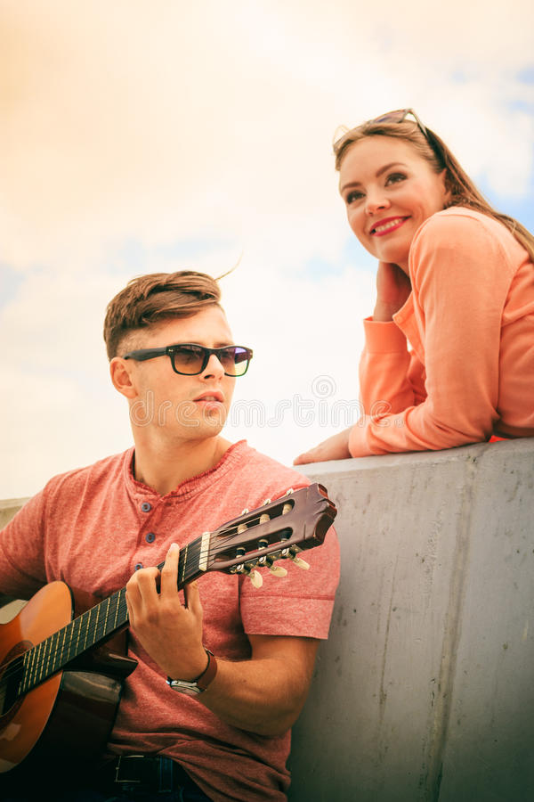 Happy couple with guitar outdoor. Musical date concept. Young happy couple with instrument men playing classic guitar dating outdoor at sea royalty free stock photos