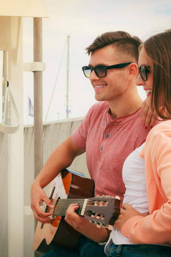 Happy couple with guitar outdoor. Musical date concept. Young happy couple with instrument men playing classic guitar dating outdoor at sea stock photography