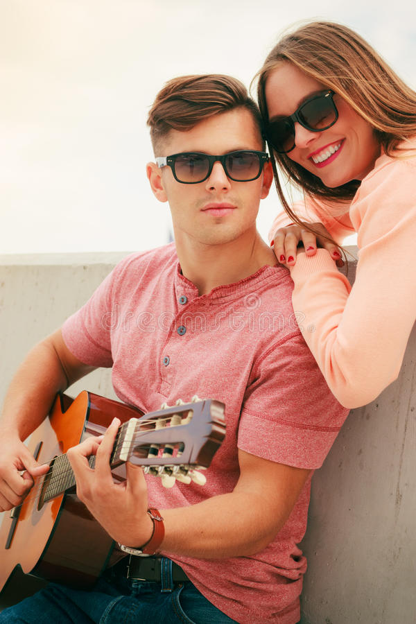 Happy couple with guitar outdoor. Musical date concept. Young happy couple with instrument men playing classic guitar dating outdoor at sea stock images