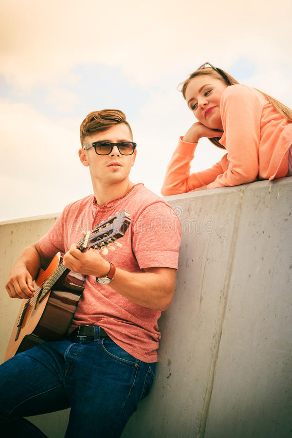 Happy couple with guitar outdoor. Musical date concept. Young happy couple with instrument men playing classic guitar dating outdoor at sea stock photos