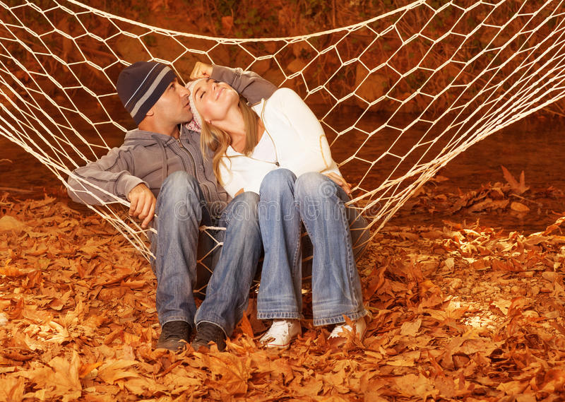 Happy couple in hammock. Image of happy couple swinging in hammock, young family having fun in autumn park, best friends resting outdoors, cute lovers hugging on royalty free stock images