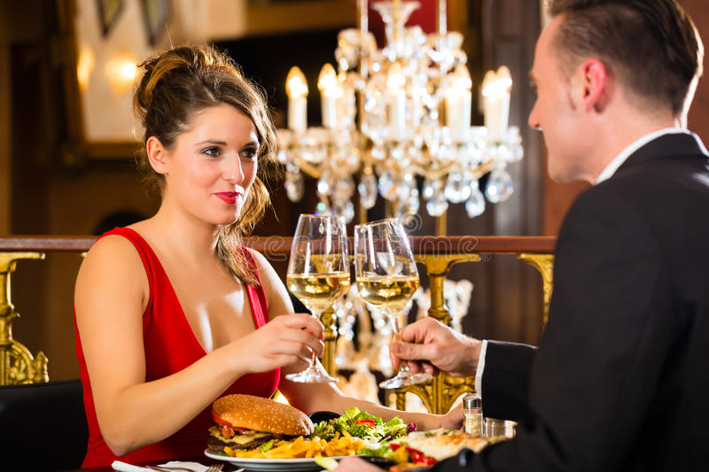 Happy couple have a romantic date in restaurant. Happy couple have a romantic date in a fine dining restaurant, a large chandelier is in Background stock images