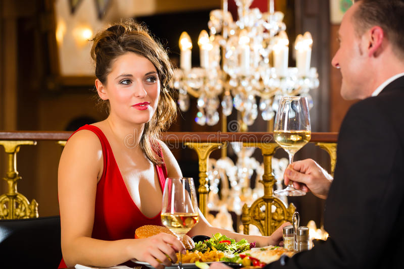 Happy couple have a romantic date in restaurant. Happy couple have a romantic date in a fine dining restaurant, a large chandelier is in Background royalty free stock photo