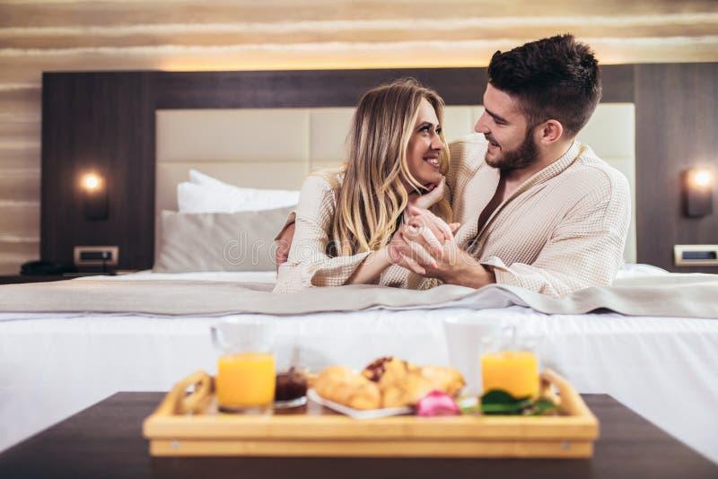 Happy couple having breakfast in luxury hotel room stock image