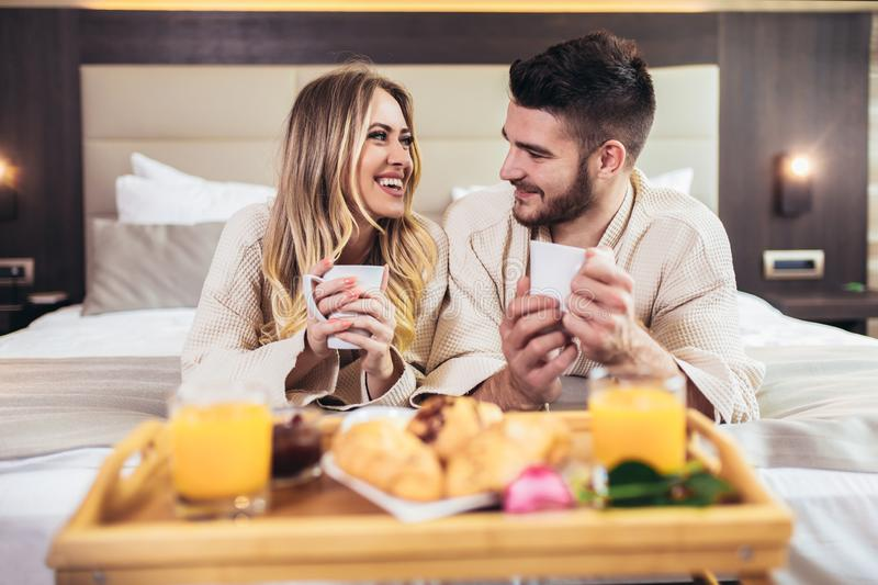 Happy couple having breakfast in luxury hotel room stock images