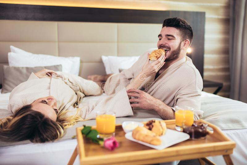 Happy couple having breakfast in luxury hotel room stock photo